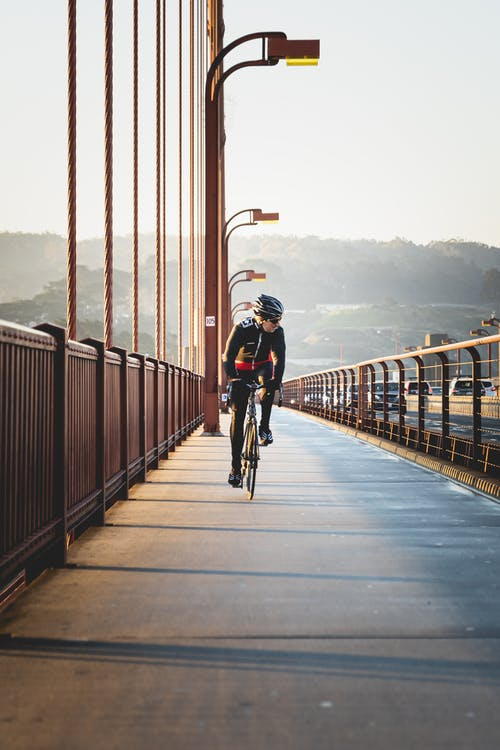 Man Riding a Bicycle on Bridge