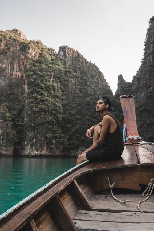 Man in Black Tank Top Sitting on Brown Boat on Body of Water