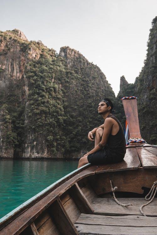 Man in Black Tank Top Sitting on Brown Boat on Body of Water