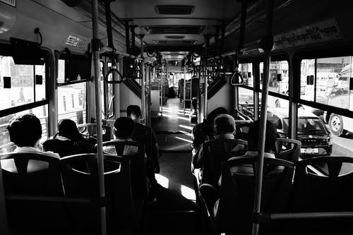 Grayscale Photo Of People Sitting Inside A Bus