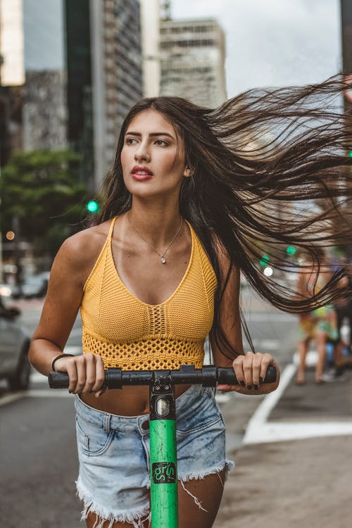 Woman in Yellow Tank Top and Blue Denim Jeans Riding Bicycle on Road
