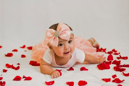 Baby In A Dress Lying On Petals