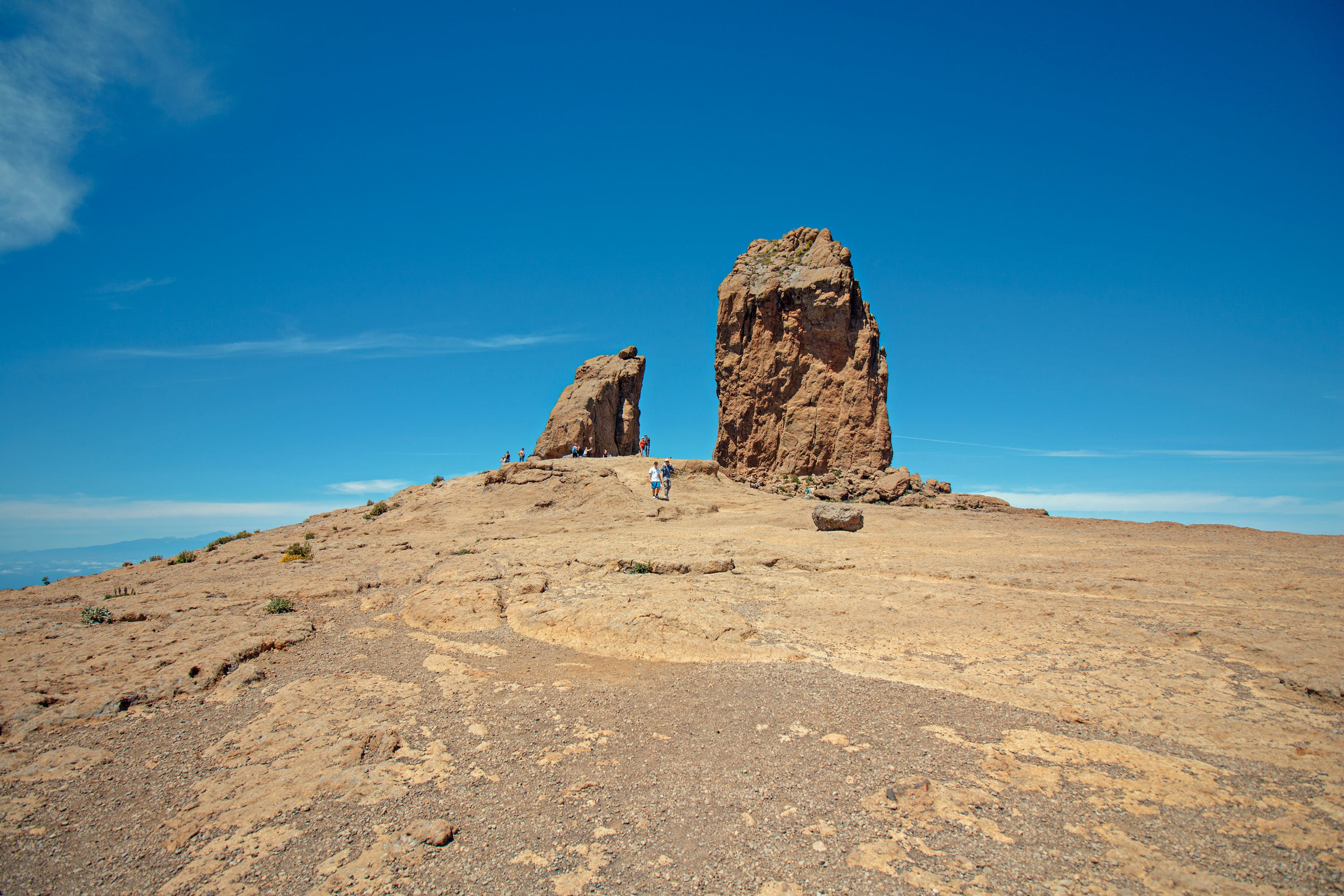 Woman Standing on Brown Mountain Under Blue Sky