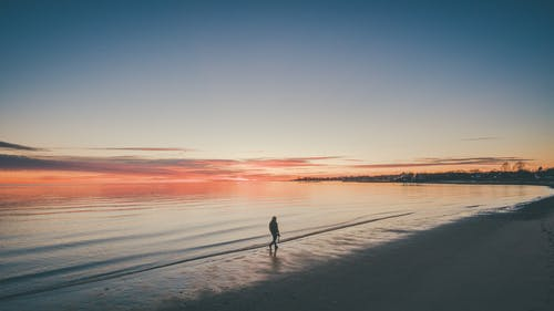 Person Walking At The Beach During Sunset