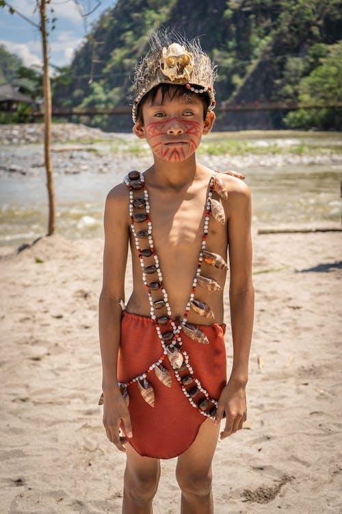 棕色串珠的项链和棕色串珠的项链,站在海滩上的女人