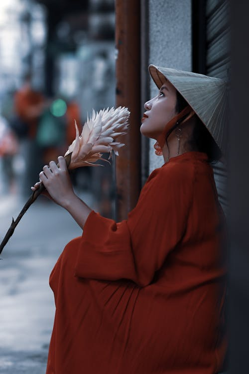 Woman In Red Coat Holding White Flower