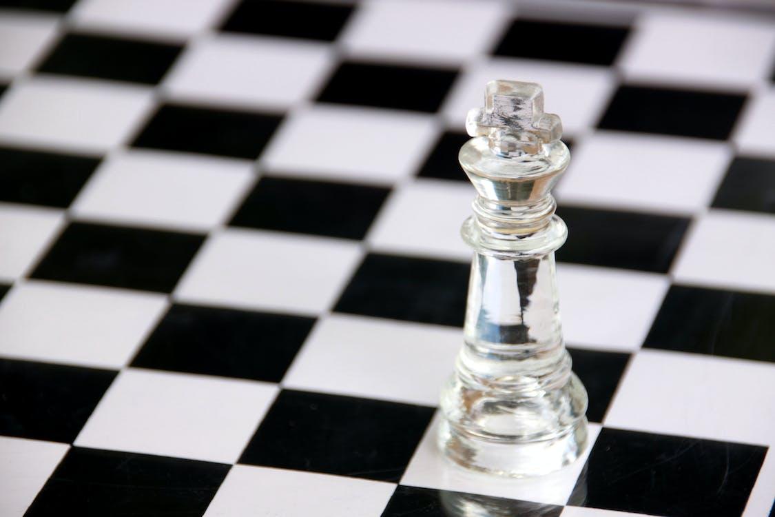 검은 색과 흰색 체크 무늬 테이블에 투명 유리 체스 조각