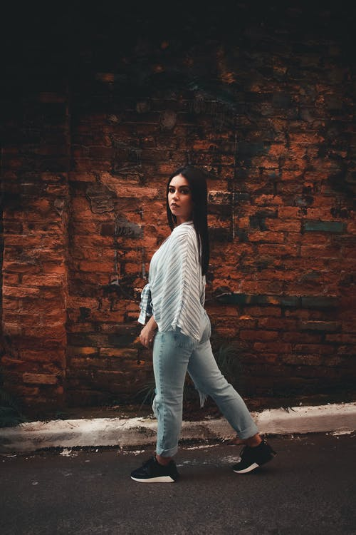 Woman in White and Black Striped  Shirt and Blue Denim Jeans Standing Beside Brick Wall