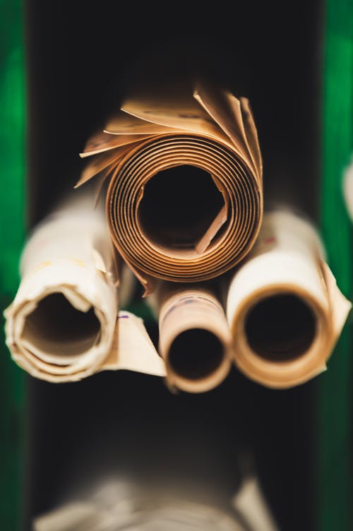 Stack of rolled paper between green walls