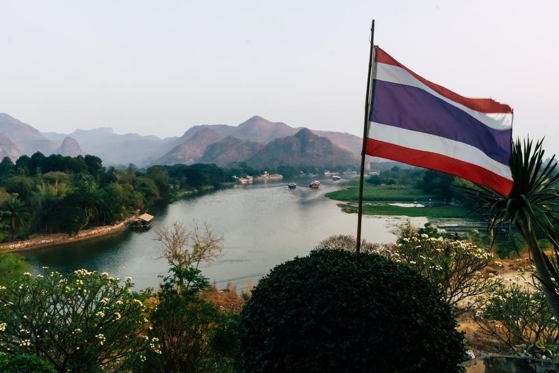Mountain and River Landscape Behind Thailand Flag