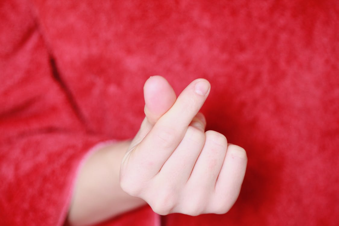 Persons Hand on Red Textile