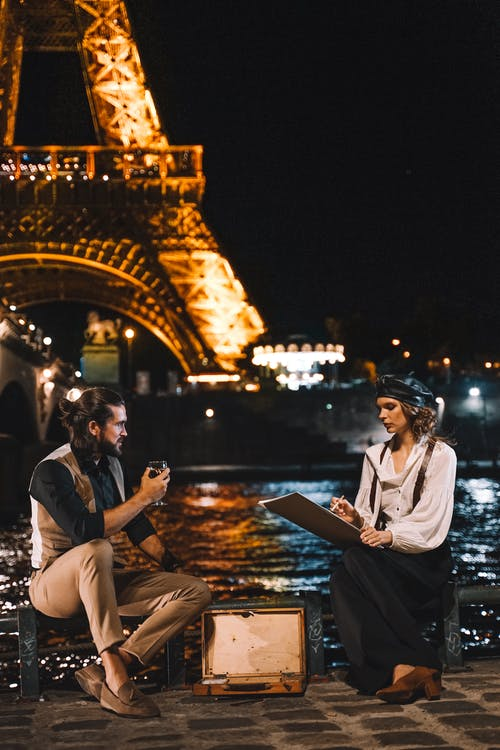 Man and Woman Sitting on Brown Wooden Dock during Night Time