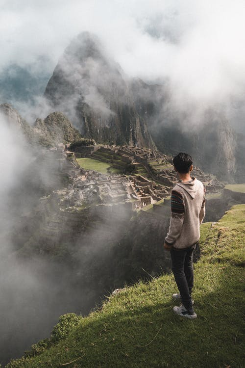 Photo of Man Standing on Cliff Edge