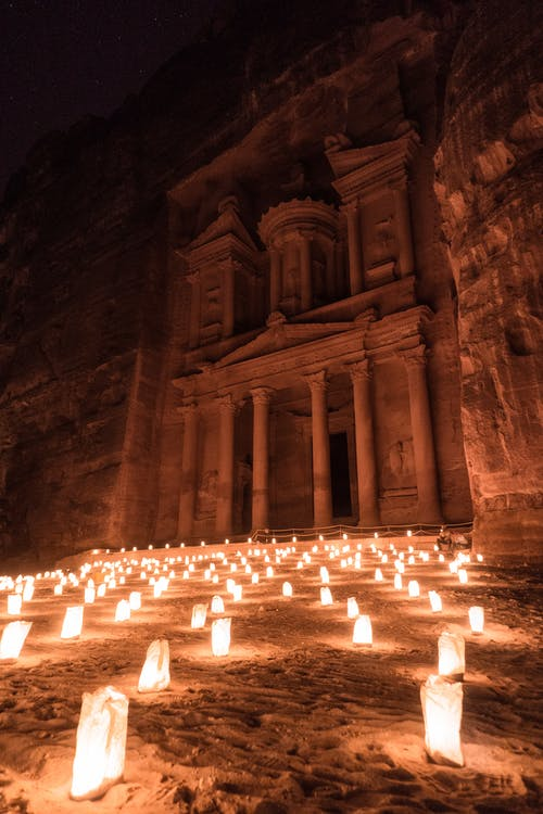 Lighted Candles in Front of Ancient Monastery Carved in the Rock