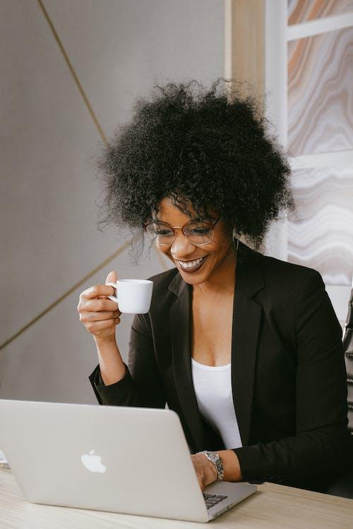 拿着白色陶瓷杯的黑色西装外套的女人