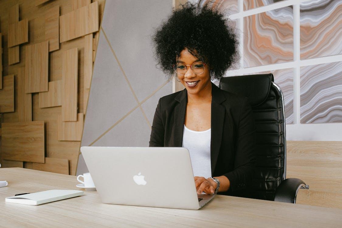 Femme En Blazer Noir Assis Près De La Table Lors De L'utilisation De Macbook