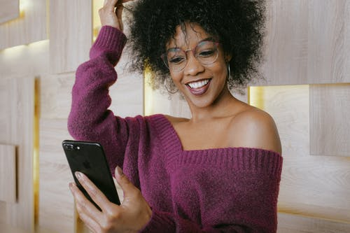 Smiling Woman in Purple Sweater Holding Black Iphone 5