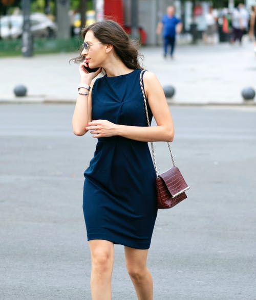 Woman Wearing Blue Sleeveless Dress and Red Sling Bag