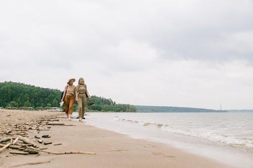 Zwei Frauen, Die Am Strand Gehen
