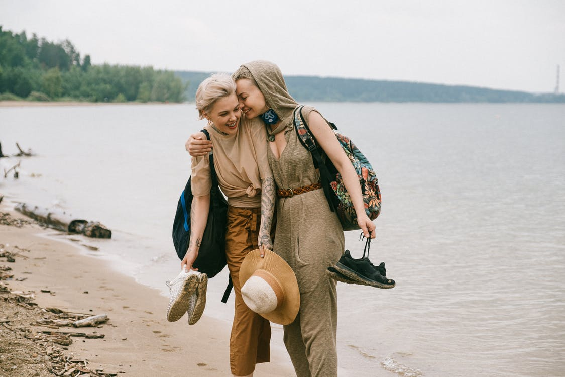 Photo of Women Embracing While Standing on Beach