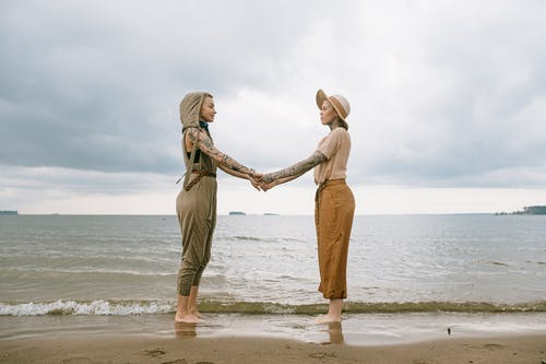 Women Holding Hands At The Beach