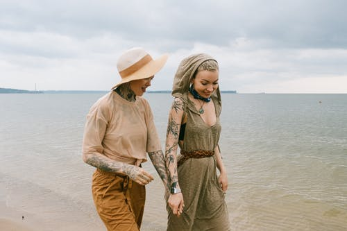 Photo of Women Holding Hands While Walking on Beach