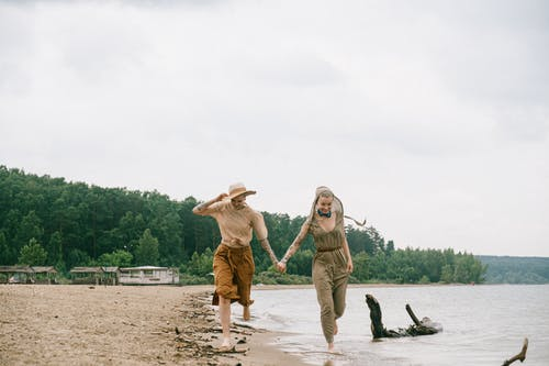 Foto Von Frauen, Die Laufen, Während Hände Am Strand Halten