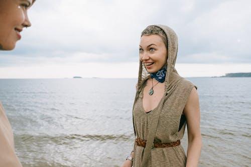 Woman in Brown Sleeveless Dress Standing on Beach