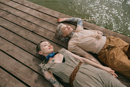 Women Lying Down on Wooden Planks