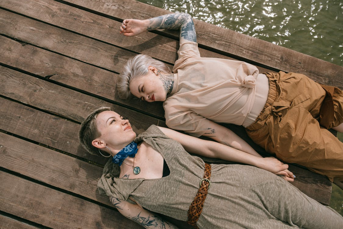 High Angle Photo of Women Lying Down on Wooden Planks