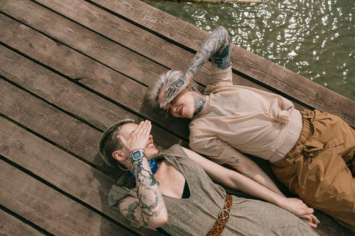 High Angle Photo of Women Lying Down on Wooden Planks While Covering Their Face
