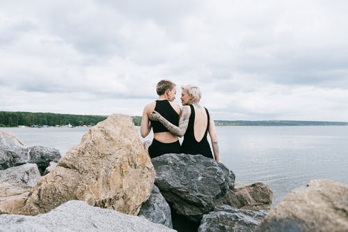 Photo of Women Sitting on Rocks Near Sea
