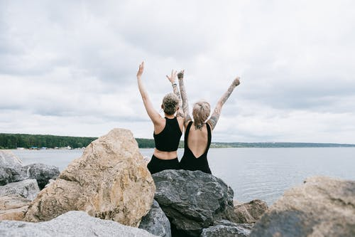Women Sitting on Rock While Raising Their Hands
