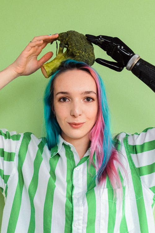 Woman In White And Green Stripe Button Up Shirt Holding A Broccoli