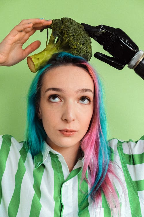 Woman In Green And White Stripe Shirt Holding A Broccoli