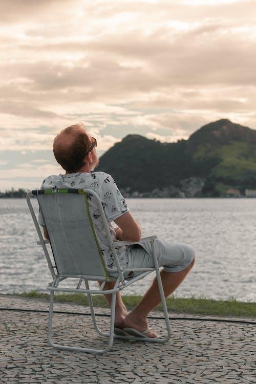 Man resting on chair near lake