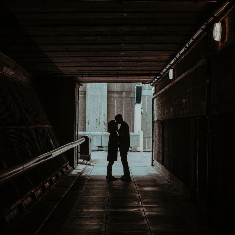 Photo of Couple Kissing in Hallway