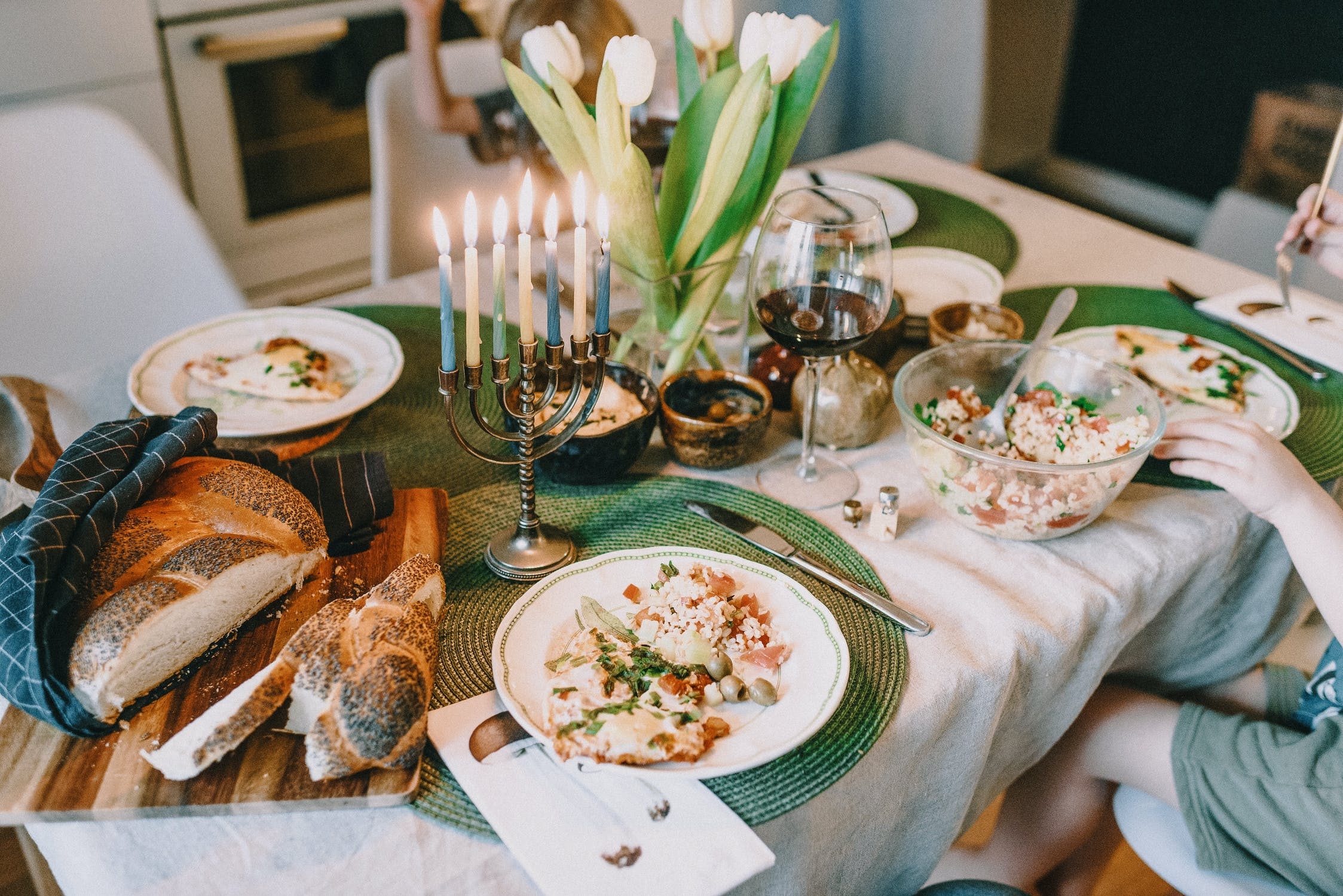 A fully lit menorah sits on a table strewn with holiday food and goodies. Photo by pexels user Ksenia Chernaya. Photo used courtesy of Pexels.com.