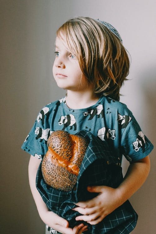 Boy In Blue Crew Neck T-shirt Holding A Bread