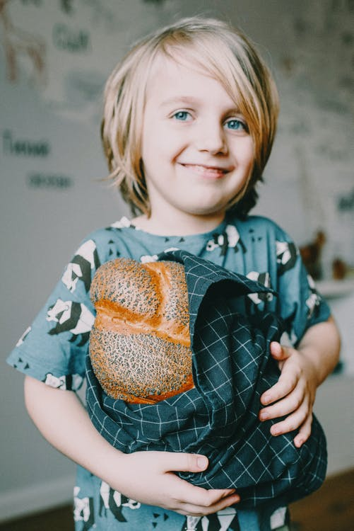 Boy In Blue Crew Neck T-shirt Holding Bread