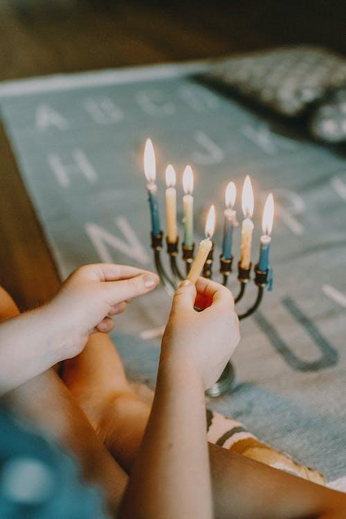 Person Lighting Menorah
