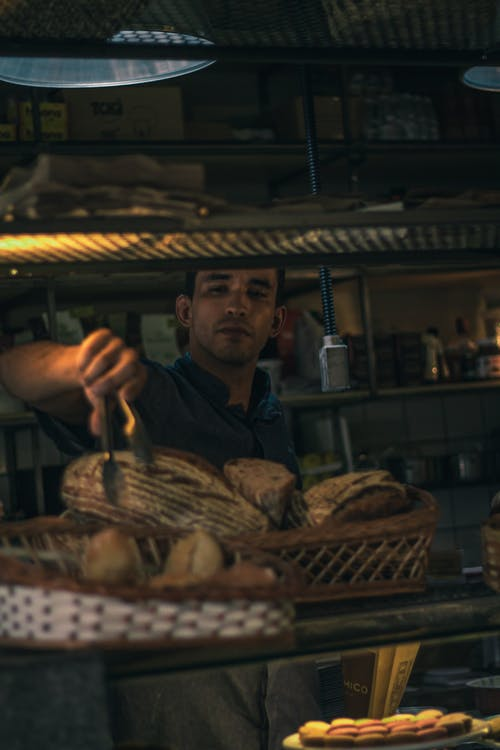Man in Blue Button Up Shirt Picking Bread with Tongs