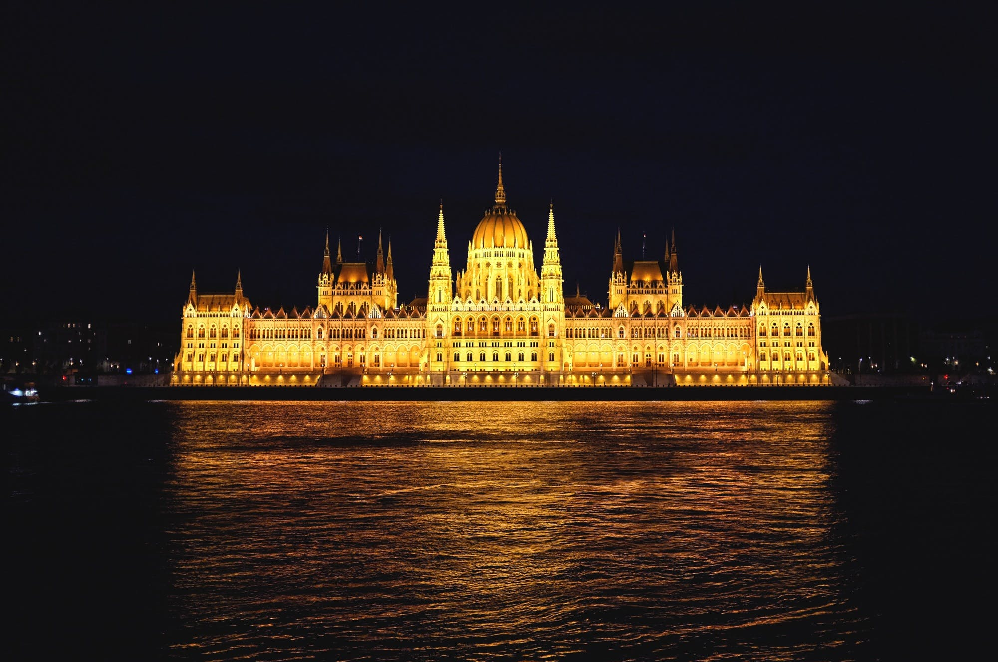 Yellow Castle Near Body of Water at Night Time
