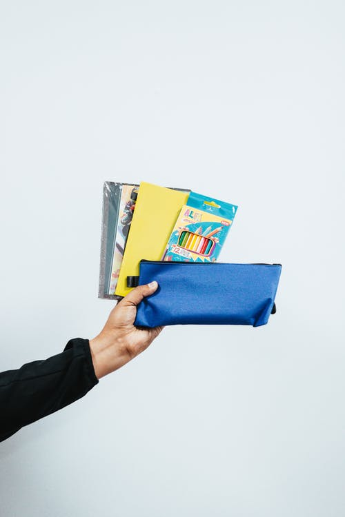 Person Holding Blue Pouch And Colored Pencils