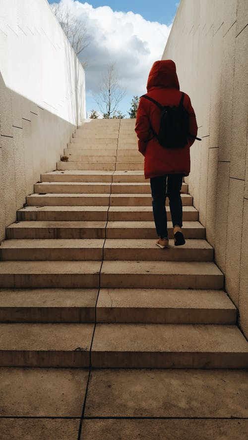 Person In Red Jacket And Black Pants Going Up The Staircase