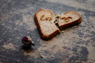 Dry Rose Flower Next to Broken Heart-shaped Cookie
