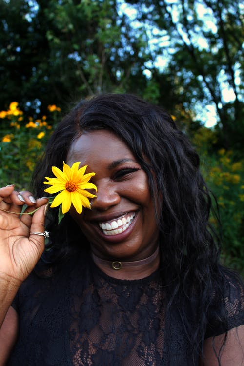 Smiling Woman Holding Yellow Flower