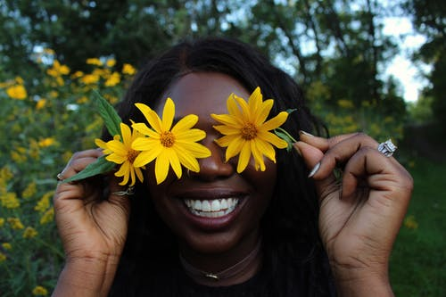 African American woman with flowers in park
