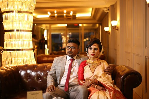 Man in Suit Sitting Beside Woman in Sari