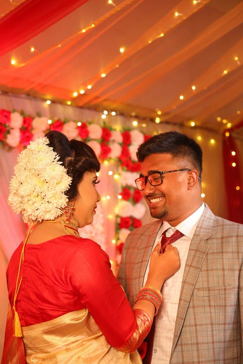 Cheerful young Indian bride in traditional wedding dress tying tie of smiling groom during wedding ceremony